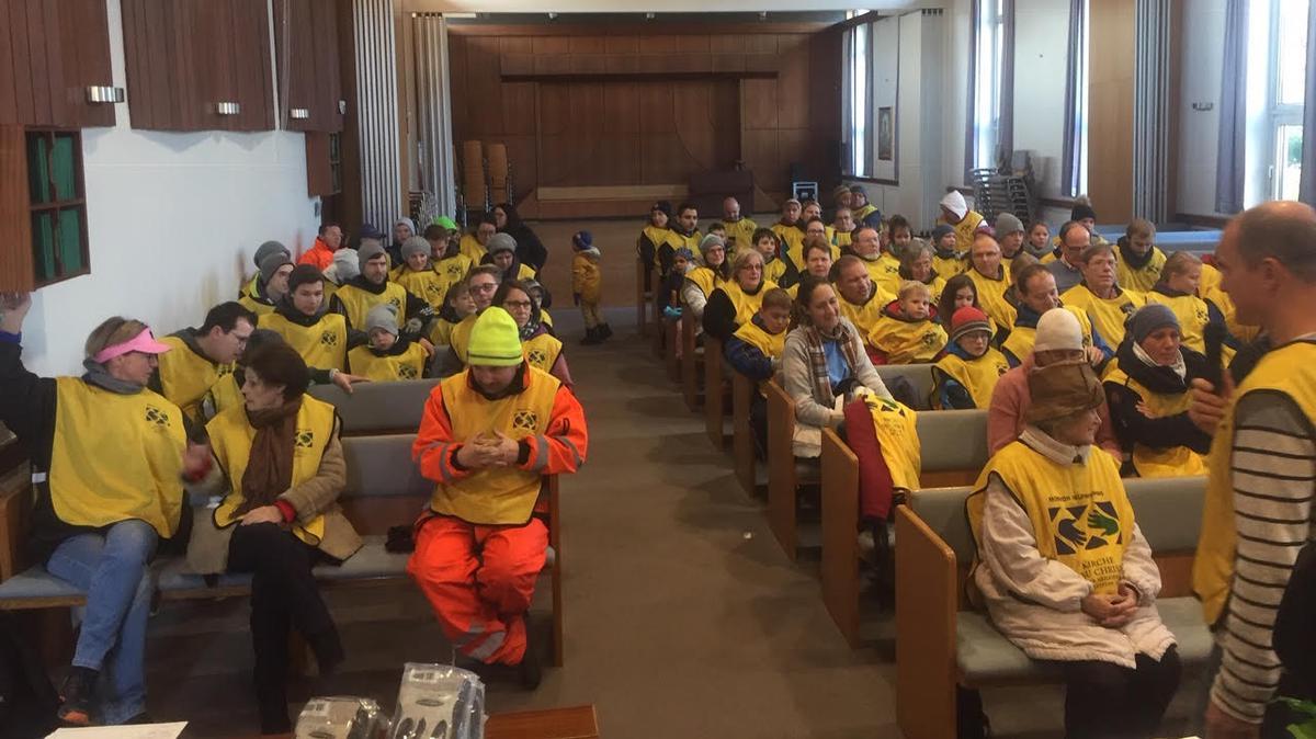 """Ausgestattet mit den gelben """"Helping Hands""""-Westen, trafen sich die Gemeindemitglieder frühmorgens in der Kapelle, um ihre Aufgaben zugeteilt zu bekommen und für den Erfolg ihrer Aktion zu beten."""