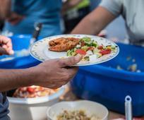 Ein Obdachloser erhält bei einem Grillfest sein Essen