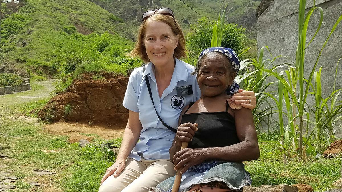 Søster Gerritsen (til venstre) sitter ved siden av Julia – en 71 år gammel kvinne med grå stær, en dårlig hofte, skadet skulder og barføtt, som daglig går opp bratte fjellsider for å komme hjem.