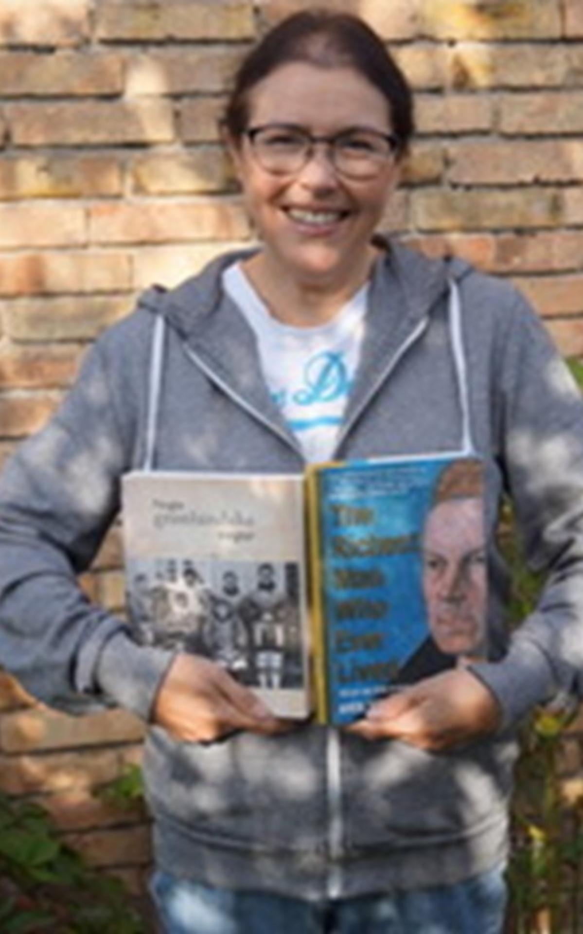 Anne drží dvě knihy obsahující její rodinnou historii