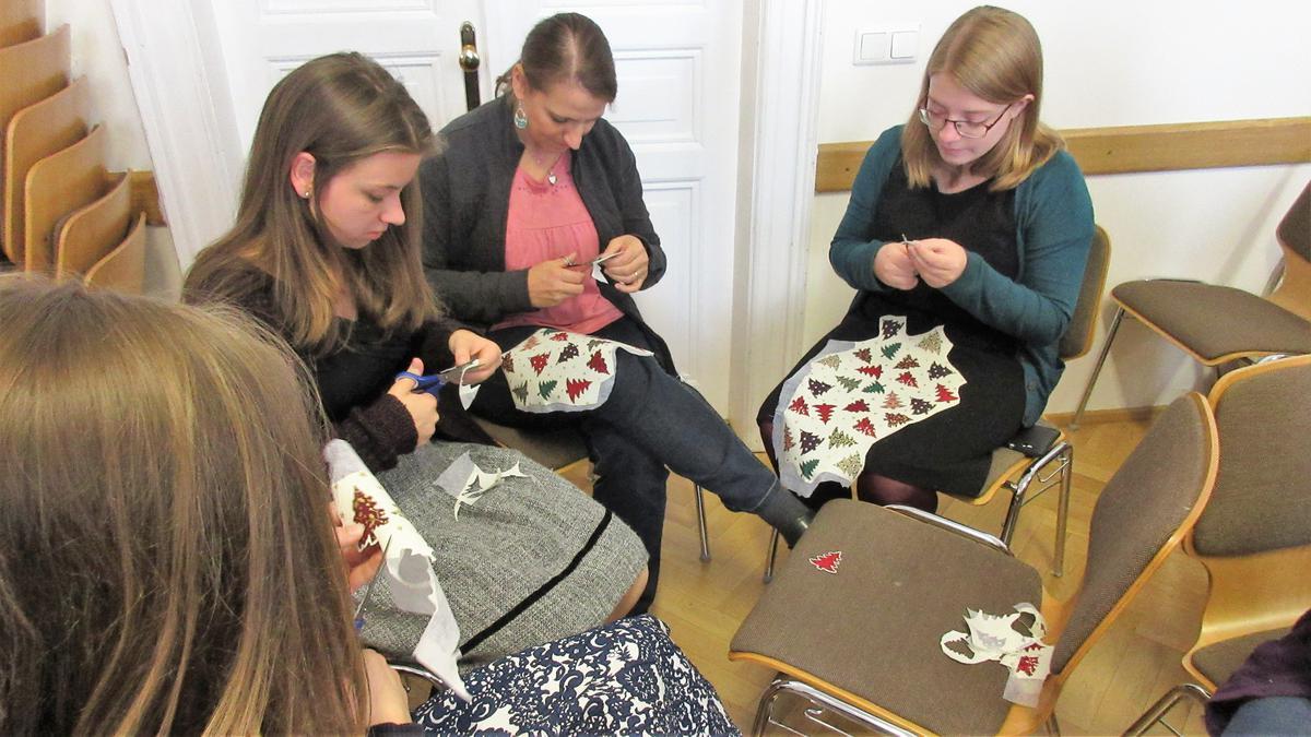 Sestry vystřihují vánoční motivy na pytlíčky