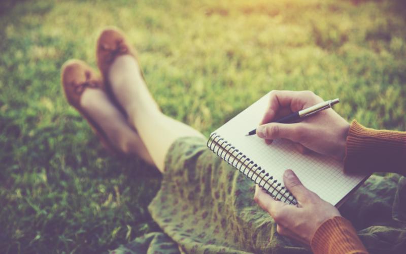 girl_notebook_writing_grass.