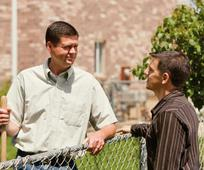 Doi bărbaţi vorbesc peste gard