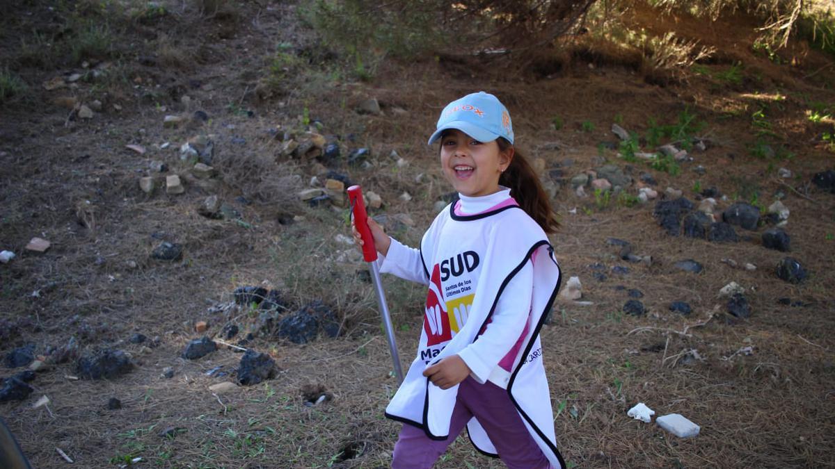 Voluntaria joven ayudando a recoger basura.