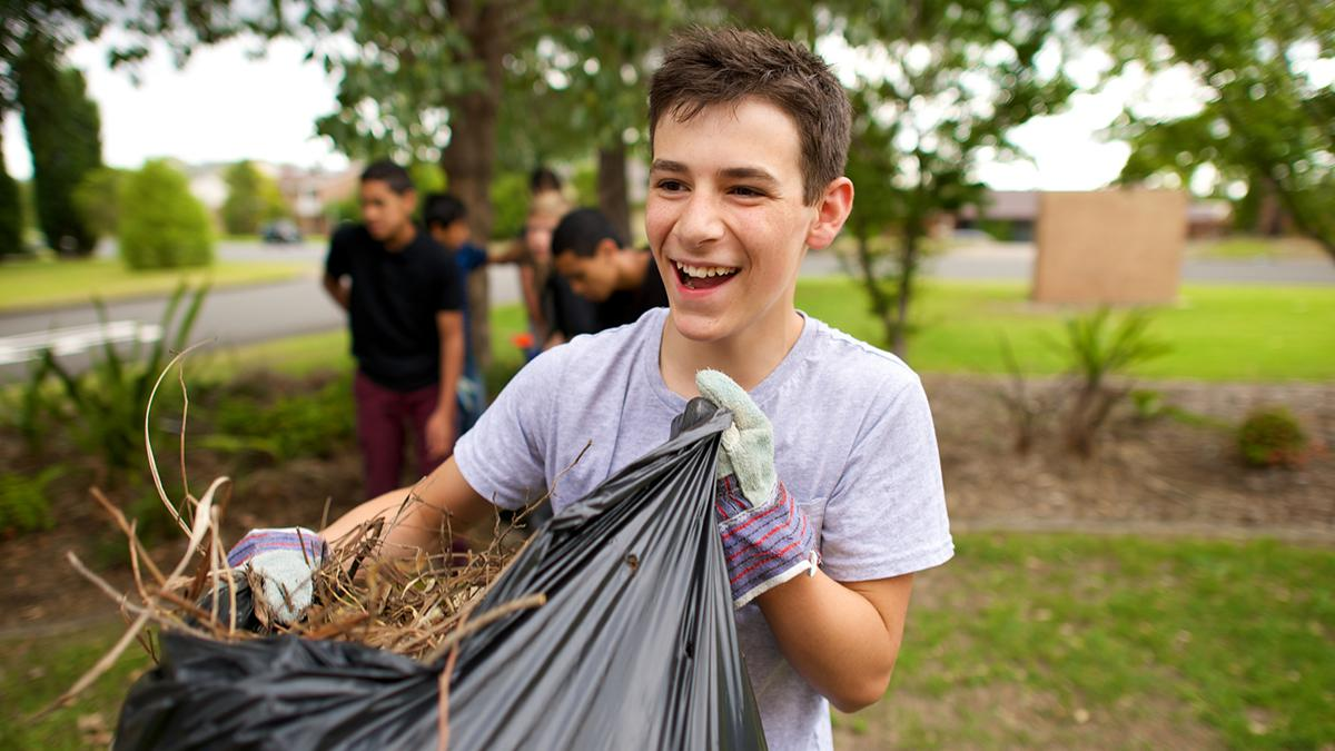 Un joven limpia de ramas un bosque