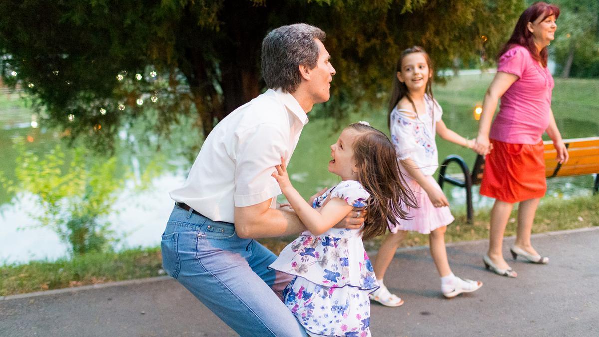 padre y madre con sus dos hijas pequeñas jugando en el parque
