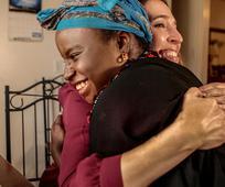Un abrazo entre dos mujeres de distintas razas