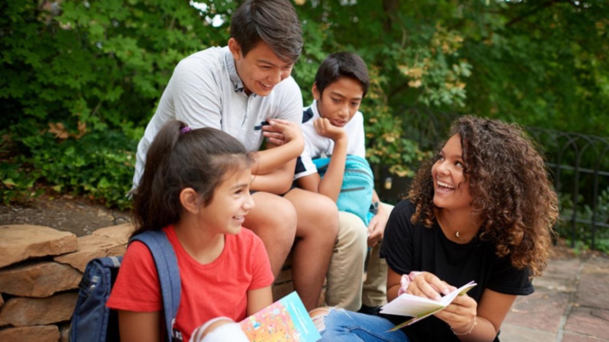 Cuatro jóvenes conversando en un parque