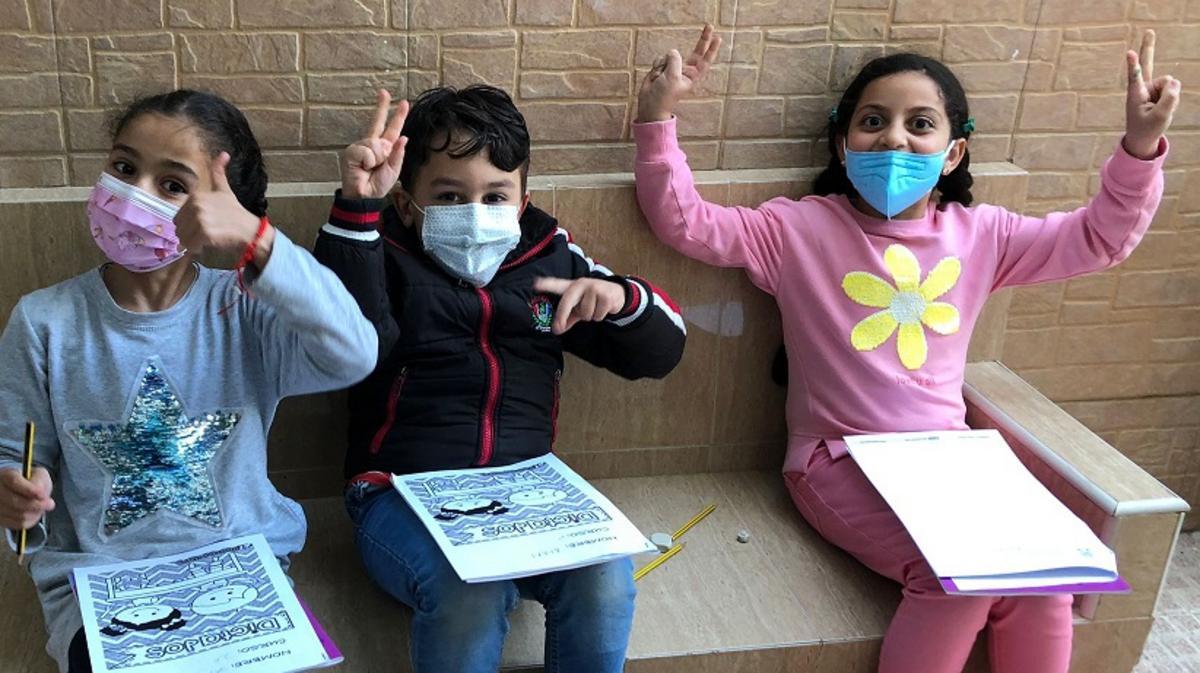 Tres niños sonrientes con sus cuadernos de ejercicios