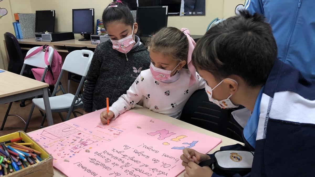 Tres niños trabajando sobre una cartulina.