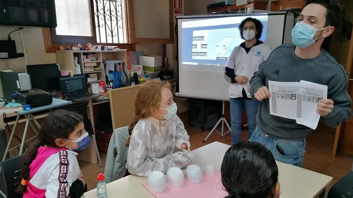 Dos personas enseñan a tres niños