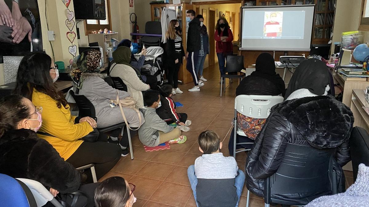 Un grupo de madres y niños reciben información sobre el centro de educación e integración Almería Acoge.