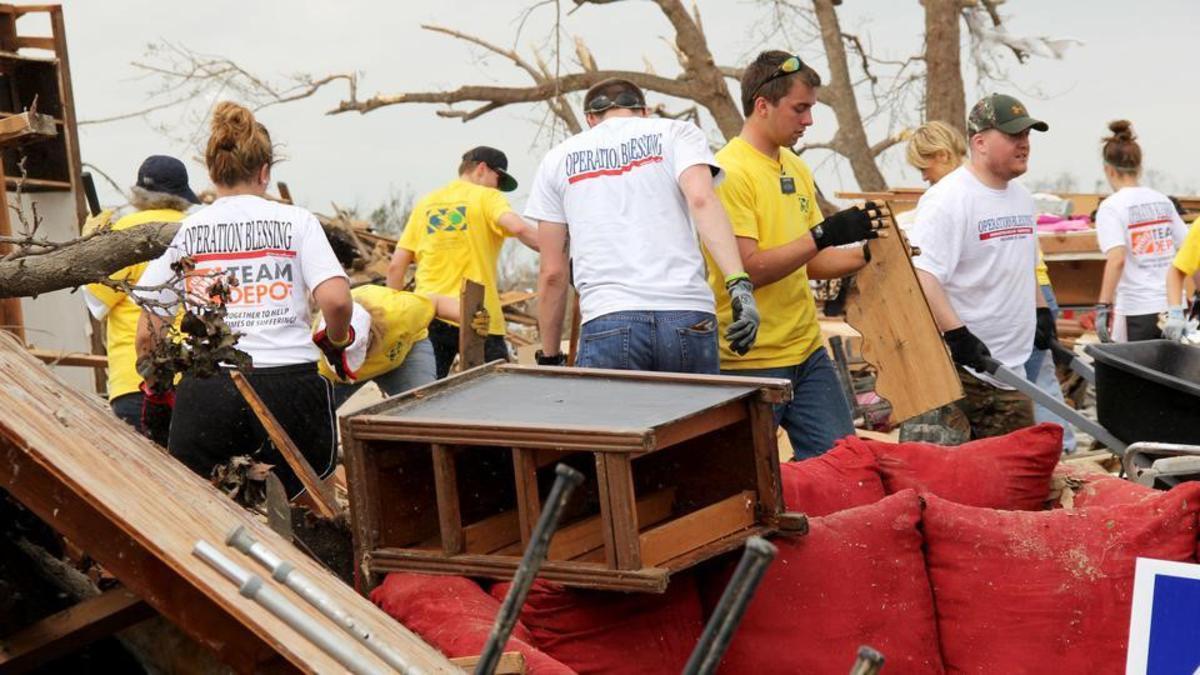 Voluntarios con chalecos de Manos que Ayudan sirviendo después de una catástrofe.
