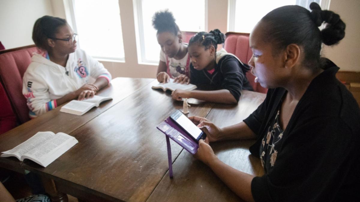 Mujeres y niñas estudiando el Evangelio en diferentes dispositivos alrededor de una mesa