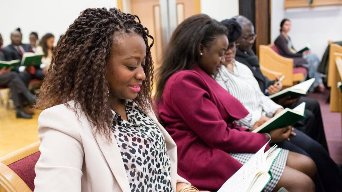Varias personas cantando un himno en un banco durante una reunión en la Iglesia