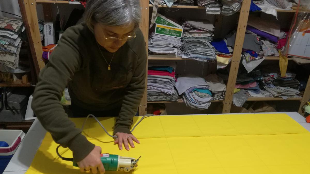 Una hermana recortando la tela para confeccionar mascarillas