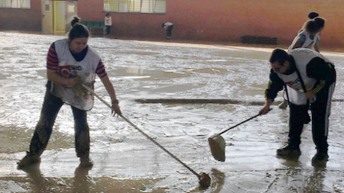 Miembros de la Iglesia barriendo el agua de las calles.