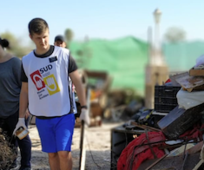 Misionero sirviendo en Elche junto a los escombros recogidos durante la ayuda a las afectados por las inundaciones.