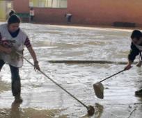 Voluntarios de la Iglesia de Jesucristo ayudando a limpiar las calles de Elche