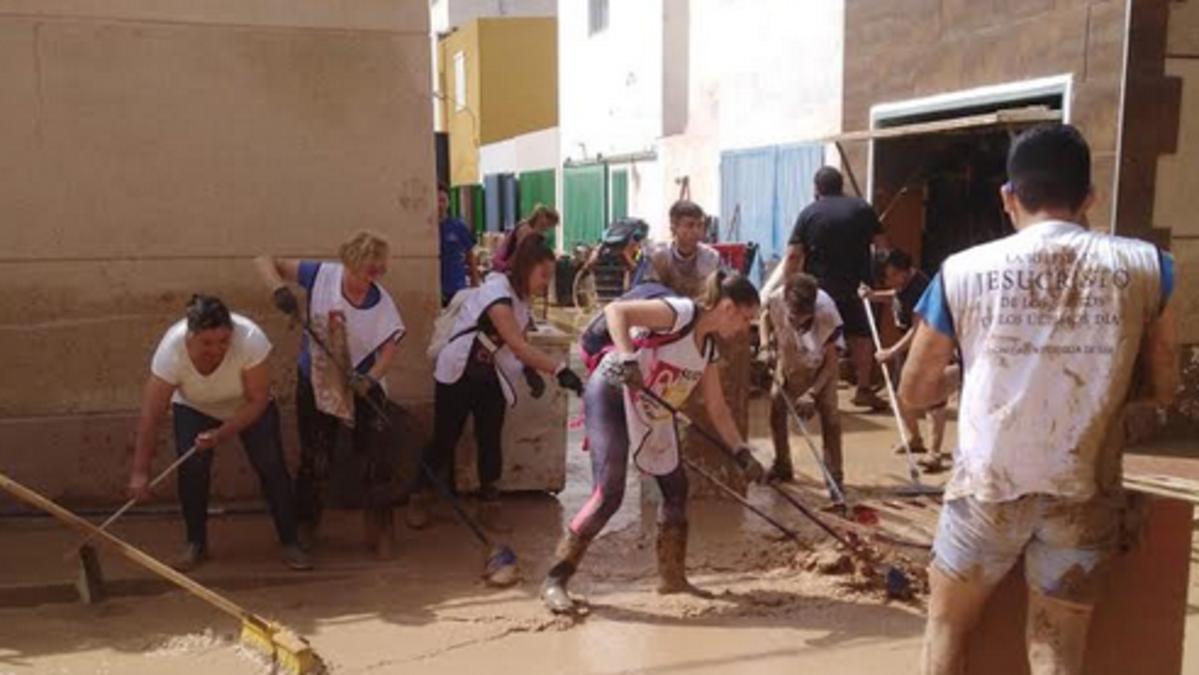 Voluntarios de la Iglesia con los chalecos Manos que Ayudan  limpiando la ciudad