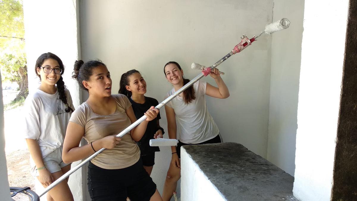 Mujeres jóvenes prestando servicio pintando paredes