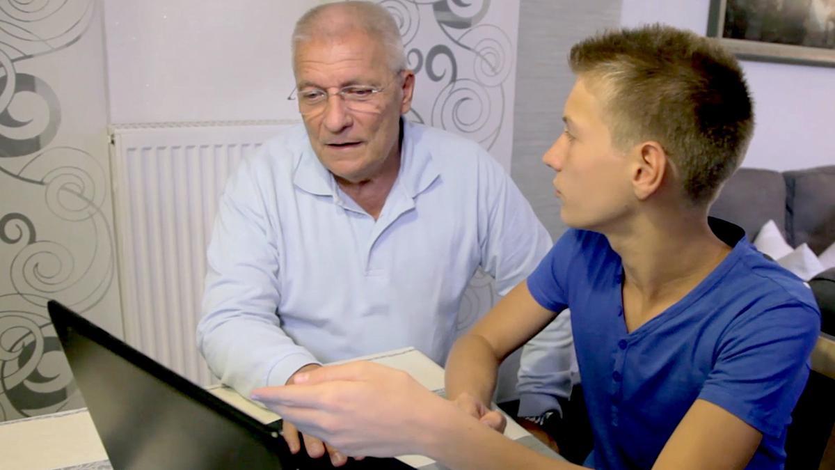 Un joven con su abuelo haciendo historia familiar en línea
