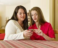 Two women browsing social media on a phone