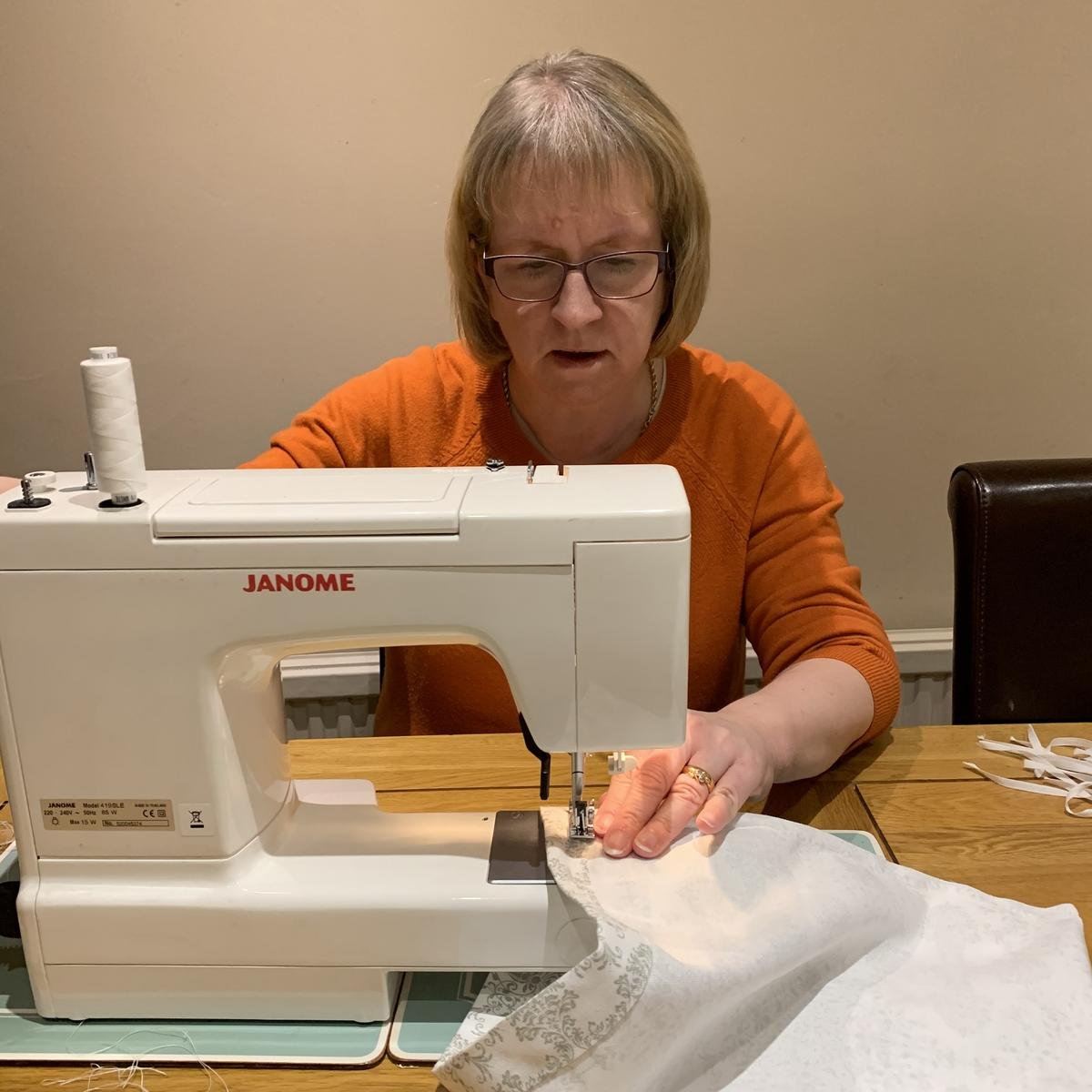 Janet Leeds sewing on sewing machine
