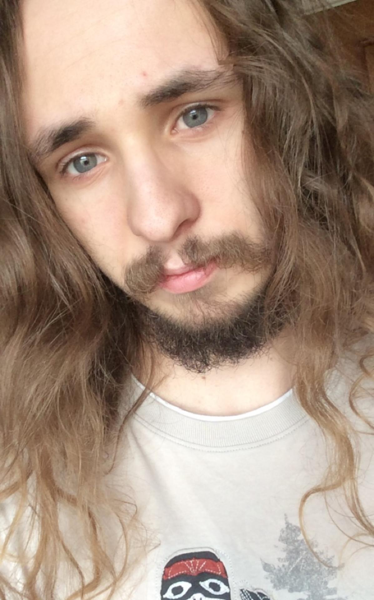 Daniel Cottam with long hair and beard