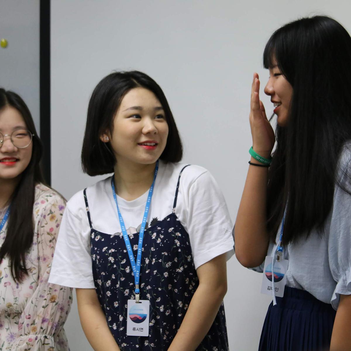 앞에 나와서 발표하는 세 명의 청녀