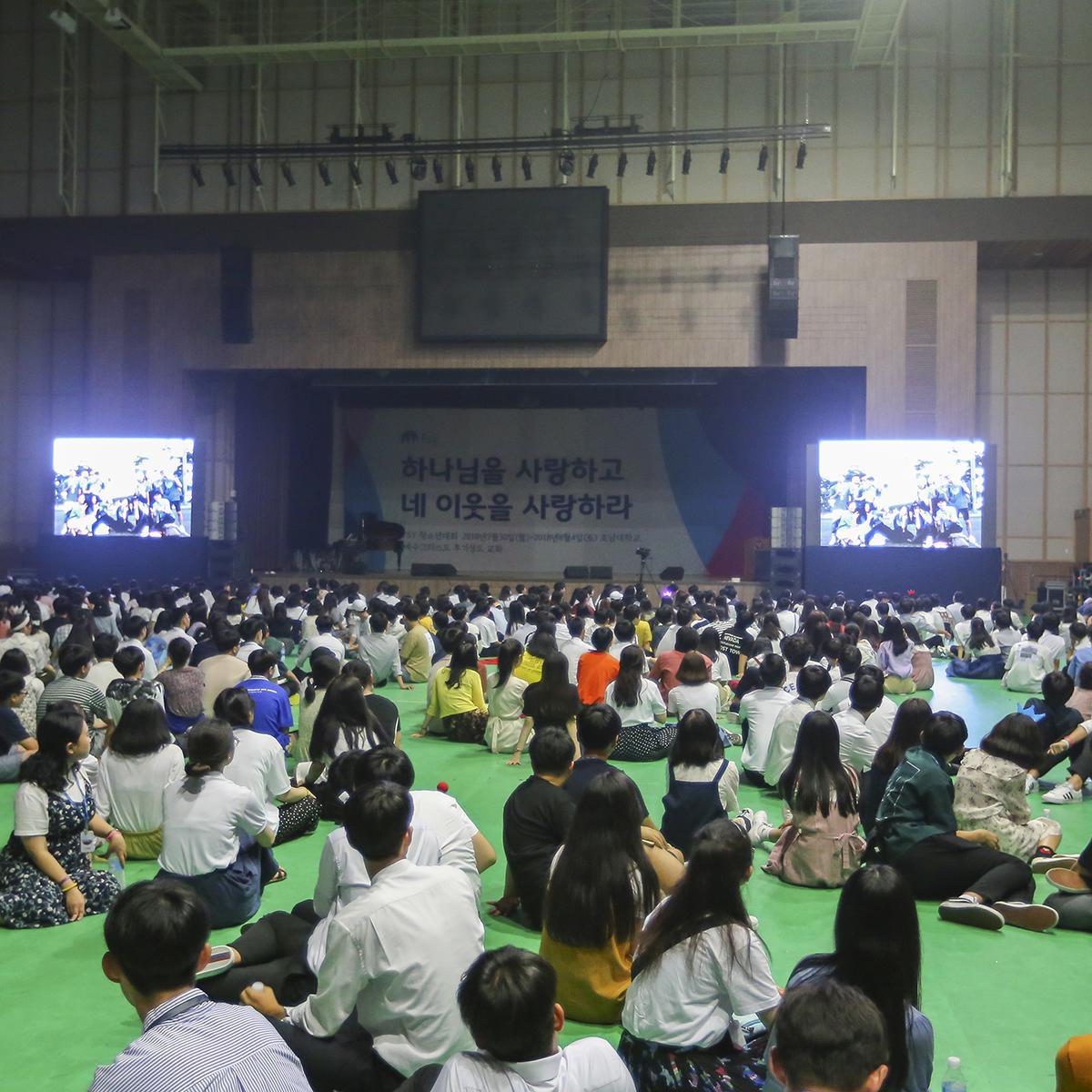 체육관에서 슬라이드쇼 감상 중인 참가자들