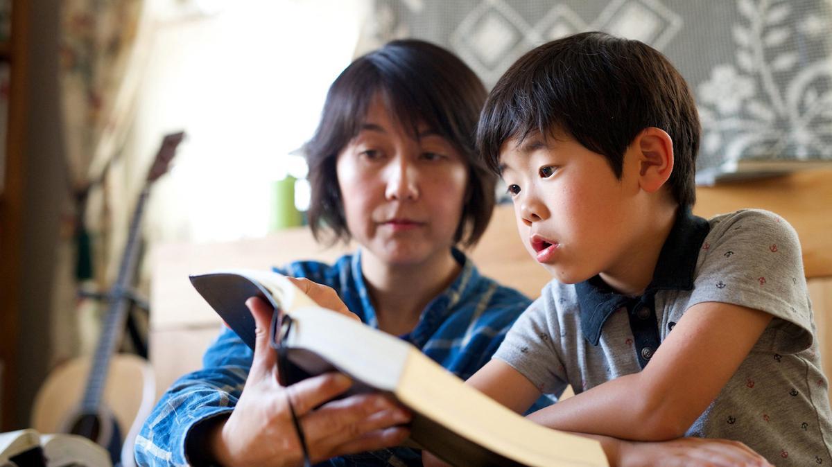 엄마와 함께 경전을 읽고 있는 아들의 모습