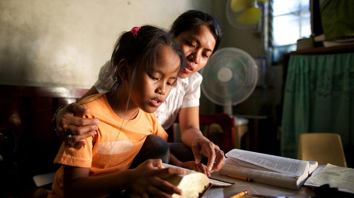 엄마와 함께 경전을 읽고 있는 딸의 모습