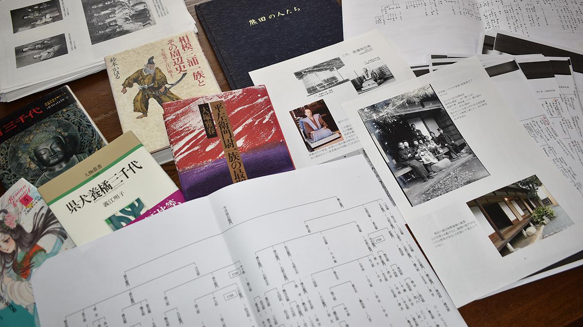 이마이 형제가 가족의 역사를 조사하며 모은 수많은 자료들. 검정색 표지가 '구마다 사람들'이라는 책으로 외가의 상세한 족보와 일화, 사진 등이 담겨있다.