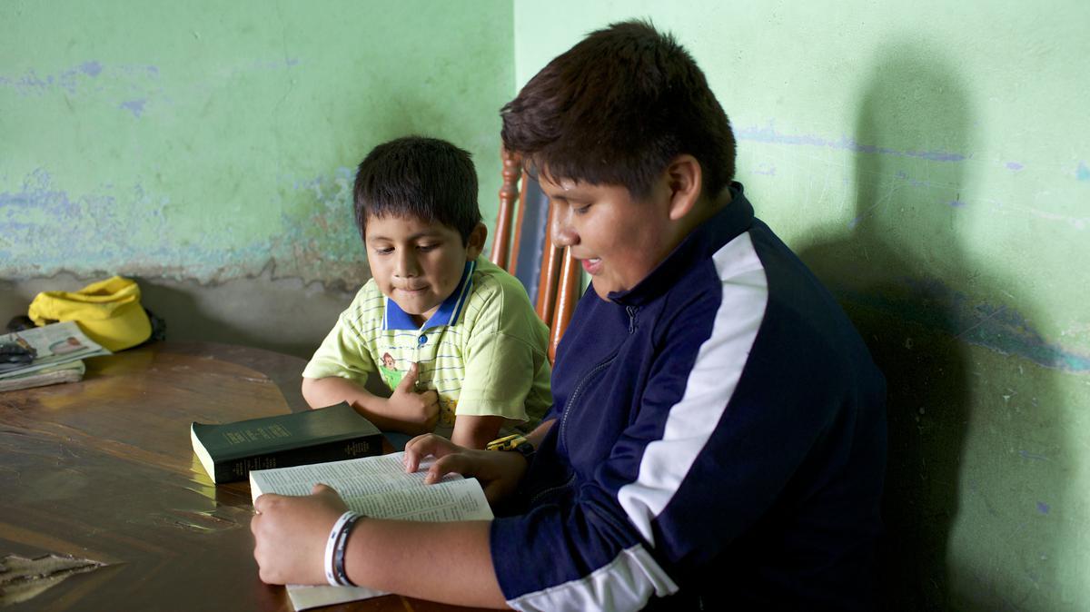 Jóvenes leyendo el Libro de Mormón.