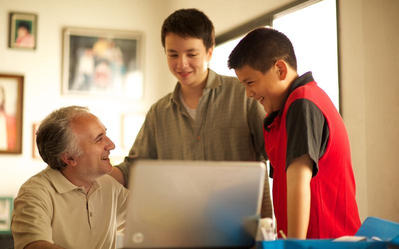 Hijos y padre riendo mientras están frente a una computadora