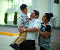 padre y madre cargando a su hijo