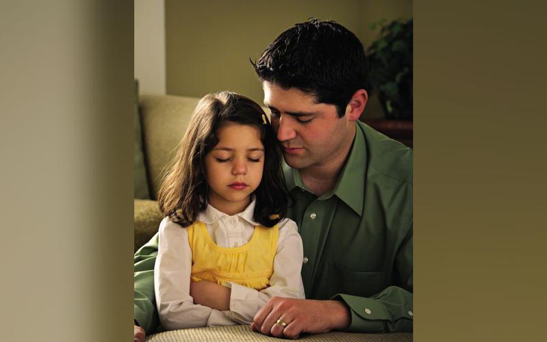 Padre orando con su hija