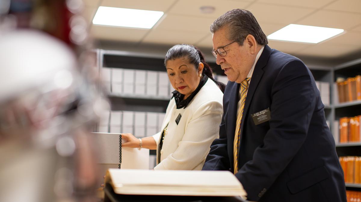 Élder y hermana Mendoza revisando archivos