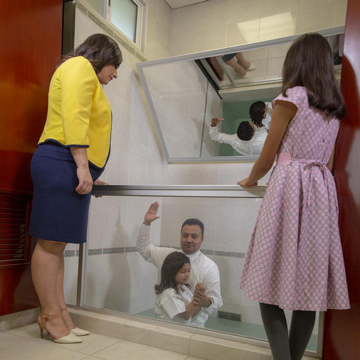 Una mujer y una niña participan como testigos en un bautismo