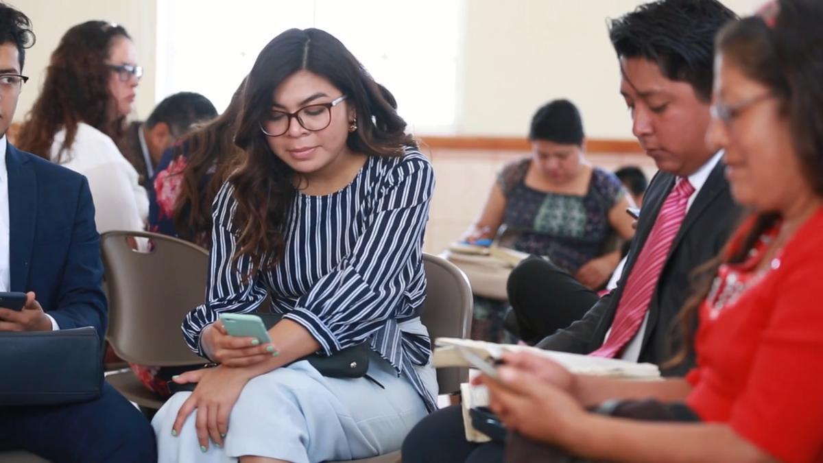 Mujer joven mirando su celular durante una clase