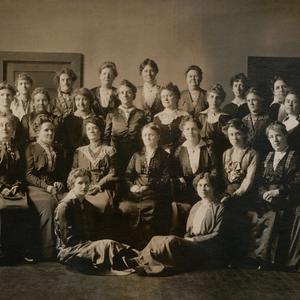 Aproximadamente en 1905. La primera Mesa Directiva General de la AMMMJ se organizó en 1880 bajo el liderazgo de ElminaS. Taylor. Las integrantes de la mesa directiva viajaban, coordinaban los esfuerzos de las asociaciones locales, mantenían correspondencia con las unidades locales, dirigían capacitaciones, desarrollaban los programas y los cursos de estudio, y hablaban en las conferencias de las Asociaciones de Mejoramiento Mutuo (AMM) que se celebraban en los meses de junio a partir de 1896. En esta foto se encuentran las siguientes mujeres que se mencionan en <i>En el púlpito:</i> MariaY. Dougall (sentada, primera por la derecha), EmmaN. Goddard (sentada, segunda por la derecha), AnnM. Cannon (sentada, tercera por la derecha), Mattie Horne Tingey (sentada, quinta por la derecha), Ruth May Fox (sentada, sexta por la derecha); May Booth Talmage (primera fila en pie, quinta por la derecha); y MinnieJ. Snow (segunda fila en pie, primera por la derecha). La hermana Tingey era la Presidenta General de la AMMMJ en el momento en que se tomó esta foto.