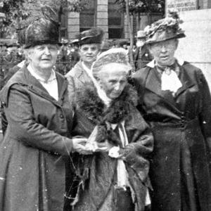 Relief Society general presidency and board members walk south on Main Street in front of their offices at the Bishop's Building. In front, left to right: Clarissa S. Williams, first counselor; Emmeline B. Wells, president; Julina L. Smith, second counselor. (PH 2032, Church History Library, Salt Lake City.)