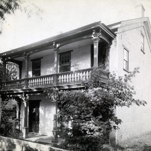 "Emmeline B. Wells lived in this two-story home at 243 State Street (or First East), Salt Lake City, between 1856 and 1888. She entertained many friends in the home, including friends of her daughters, and the Wasatch Literary Association was formed here. The garden behind the house with its fruit trees and flowers inspired her poem ""The Dear Old Garden."" Emmeline's husband, Daniel, and his other wives lived in a different house a few blocks away during this time. In a 5 July 1889 diary entry, Emmeline Wells mentioned going with photographer Charles R. Savage to have her ""dear old home"" photographed. It is not known if this is the photograph he took. (PH 2356, Church History Library, Salt Lake City.)"