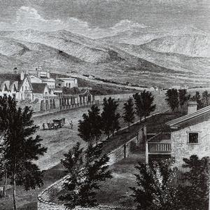 """Photograph of an engraving of South Temple Street, Salt Lake City. In the background can be seen the Lion House, Brigham Young's office, and the Beehive House. In the front on the right is the Daniel H. Wells family home. Across the street from that home (to the north, or the viewer's left), behind the stone wall, is an adobe house where Emmeline B. Wells lived between February 1888 and December 1893. The engraving was published under the title """"The Prophet's Block"""" in Randolph B. Marcy, <i>Thirty Years of Army Life on the Border</i> (New York: Harper and Brothers, 1866), p. 262."""
