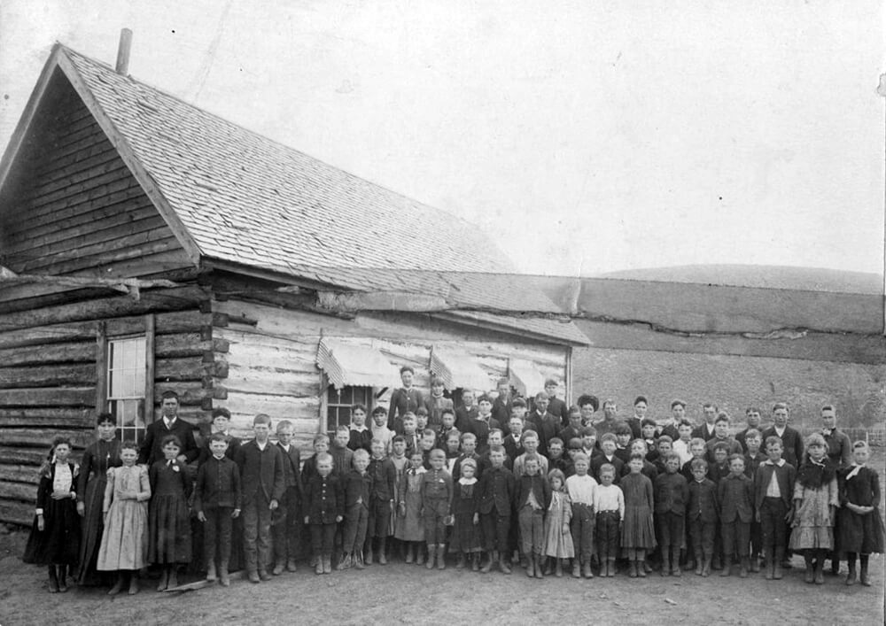 Single-story, log building with children, women, and men gathered in front