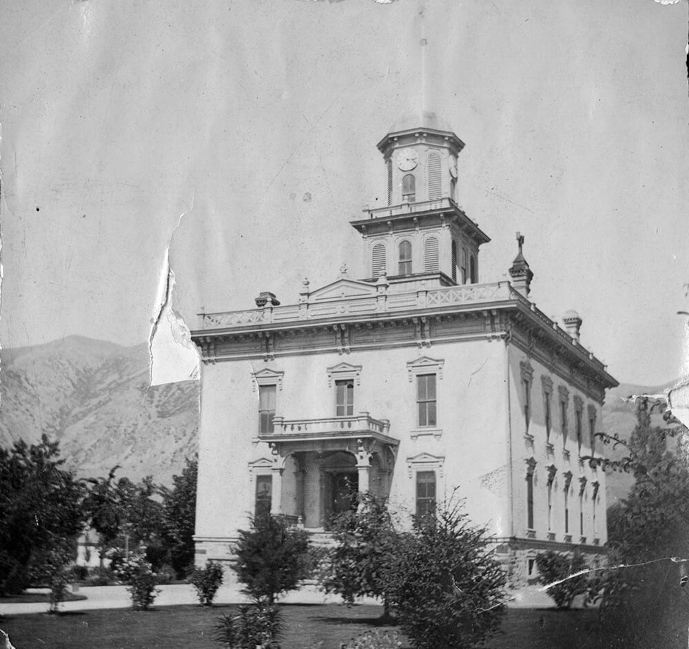 Two-story building with cupola, with mountains in background