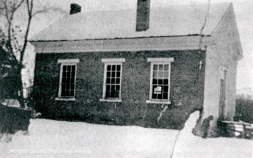 Small, single-story, brick school with chimney stacks