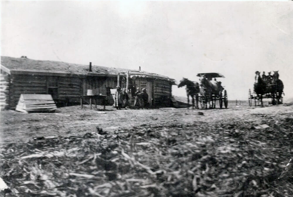Single-story log cabin with horse-drawn carriages in front
