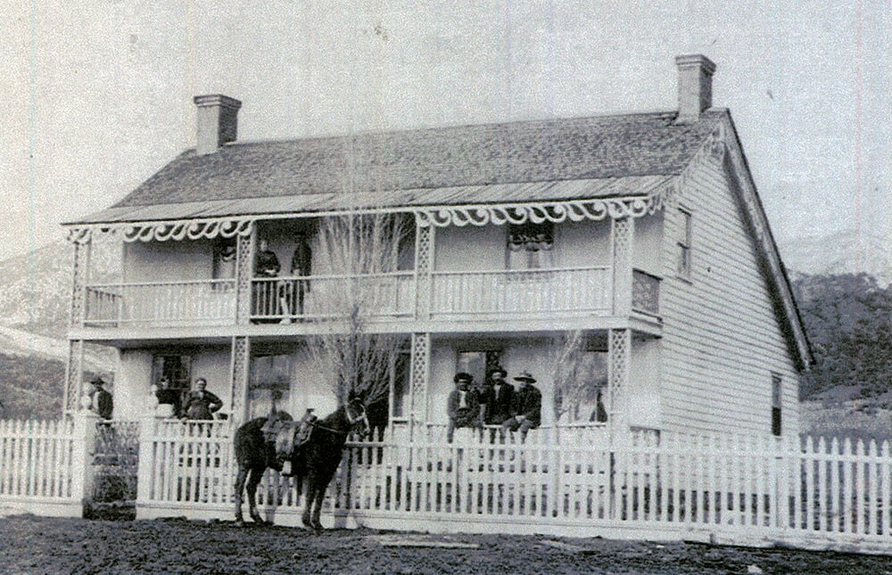 Two-story home with chimneys at each end and a balcony and porch across the front